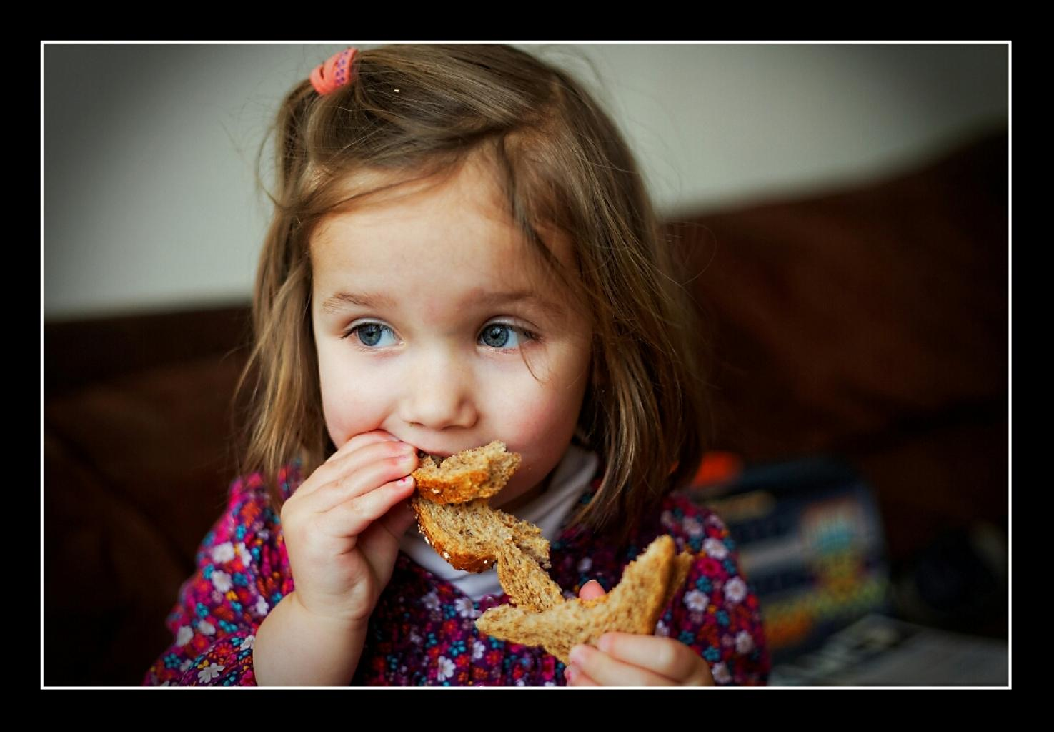 Little girl eating bread