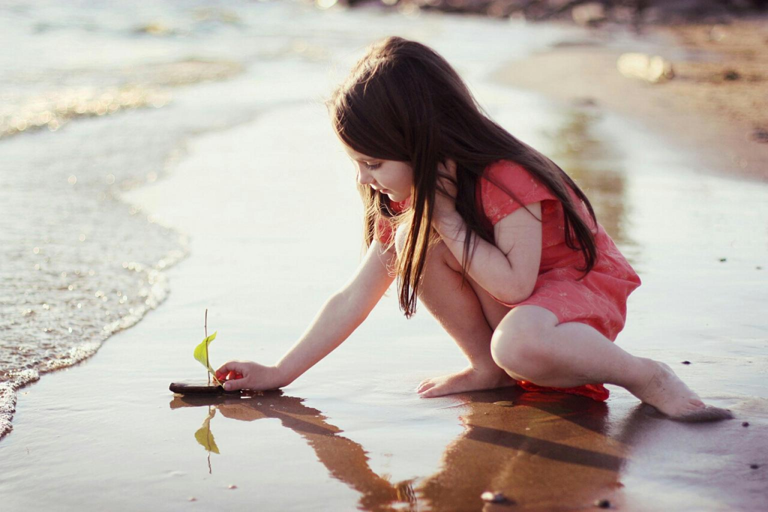 Girl playing on the beach with her little boat