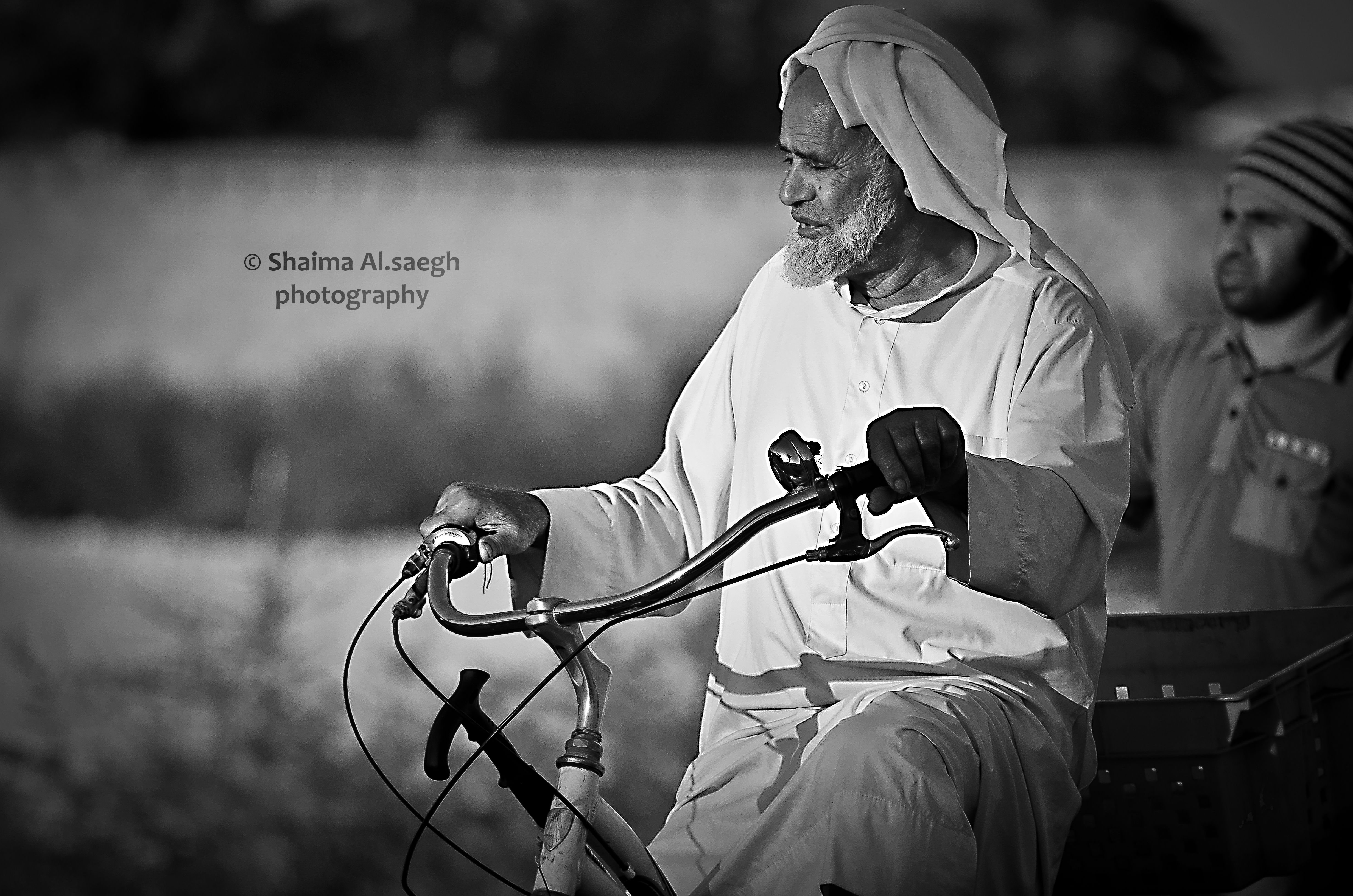 Black and white photo of an old man on bicycle