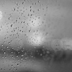 Black and white photo of rain drops on the window