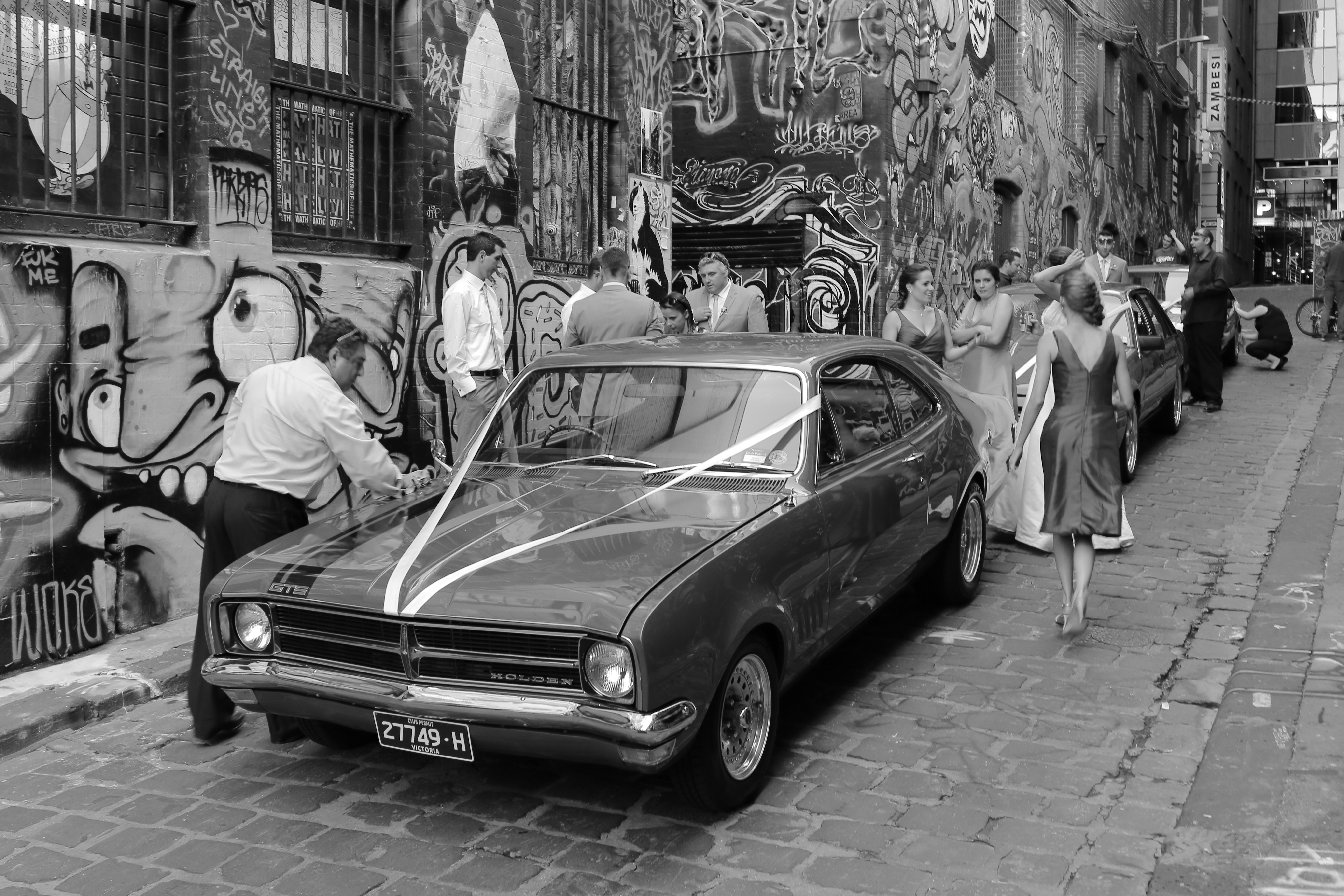 Black and white photo of a car and people around it