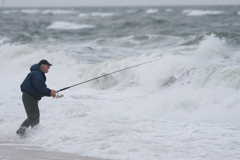 Man fishing during waves