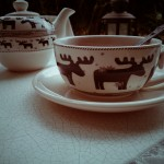 Cup and teapot with moose on the table