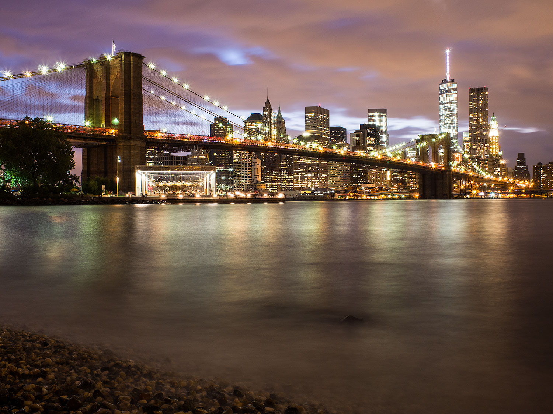 Photo of a bridge and New York at night