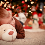 Baby with his toy around Christmas tree