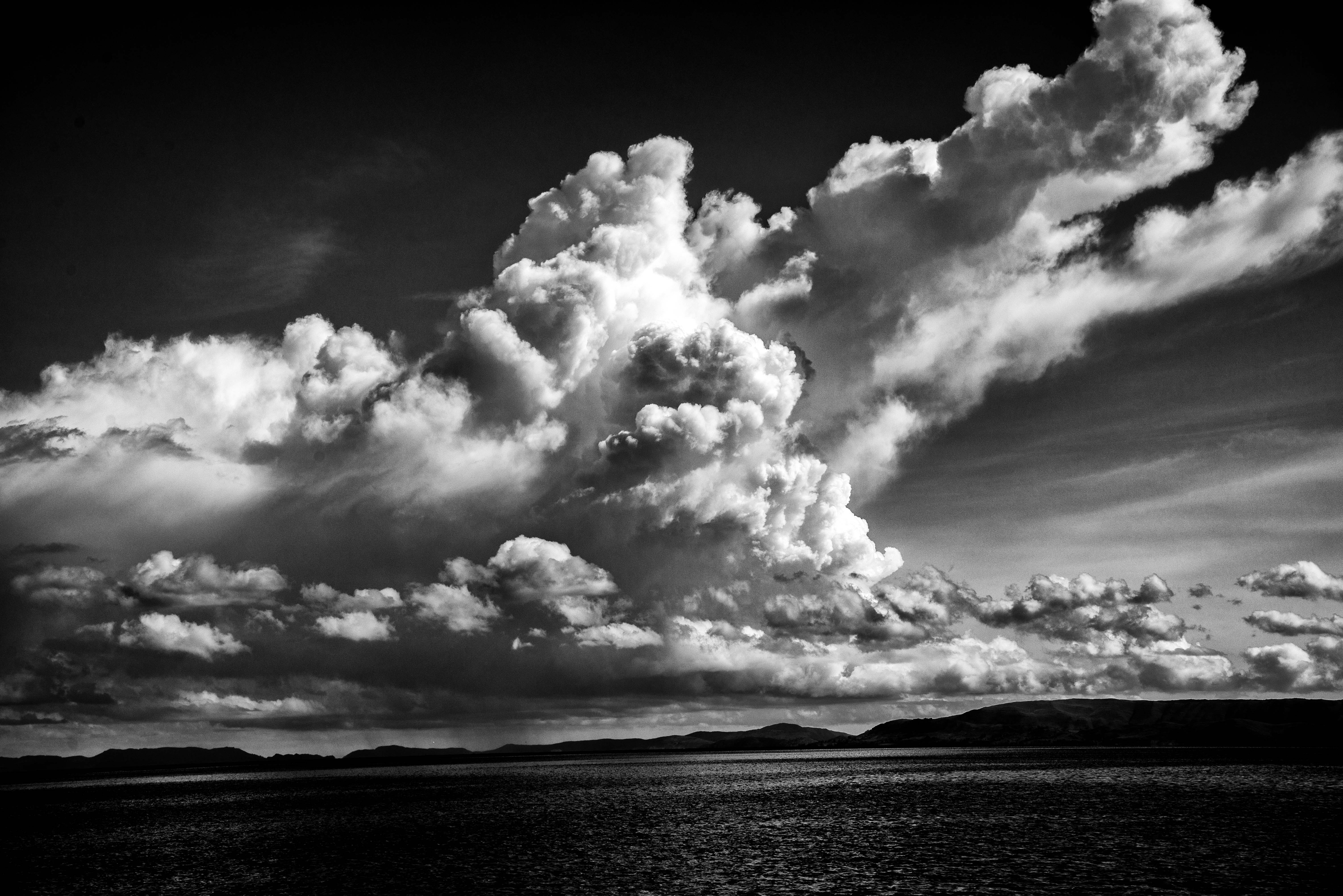 Black and white photo of clouds over the sea