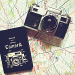 old camera and album on the map