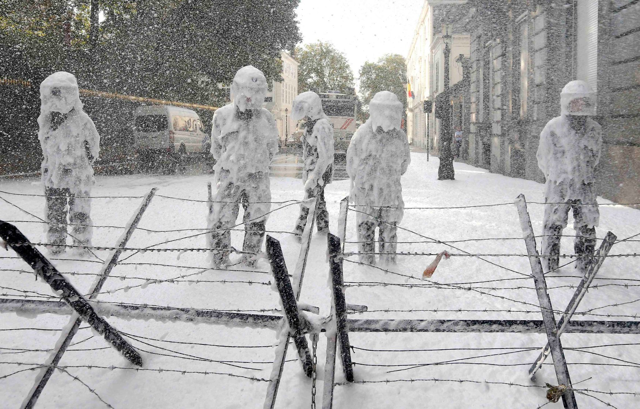 Riot Police in Foam at a Protest in Belgium | Photo by Yves Herman | Photojournalism Tips