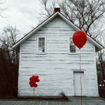 White house with red balloons in front of it