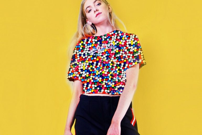a pic of blonde girl with a sprinkle of rainbows on the top and yellow background