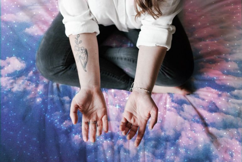 magical double exposure effect on the hands of a woman with tattoo and minimalistic rings