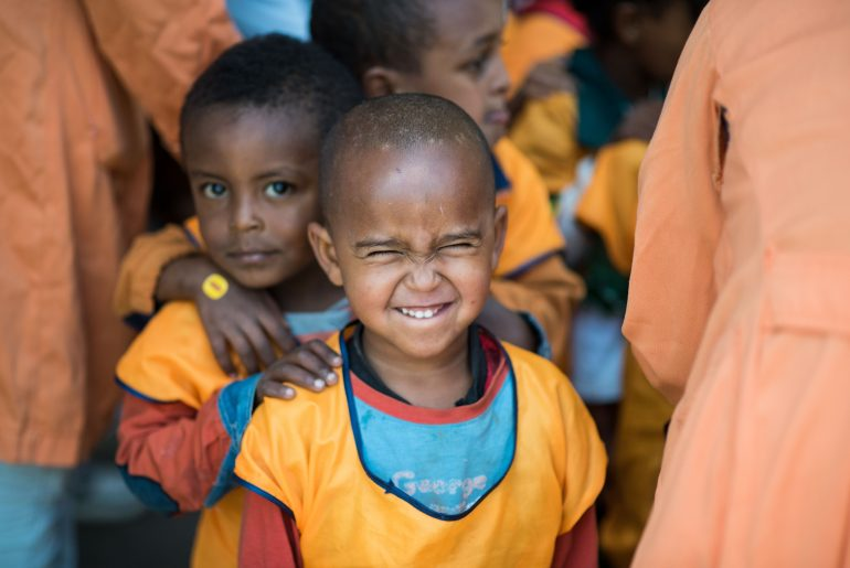afro american smiling orphan children in orange outfits