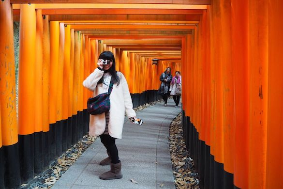 Girl in the coat taking photo, around orange fence