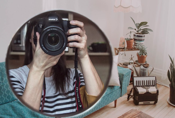 Girl with photo camera in front of the mirror
