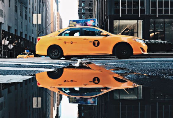 The reflection of a yellow taxi in the street
