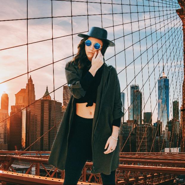 Fashionable girl poses on bridge