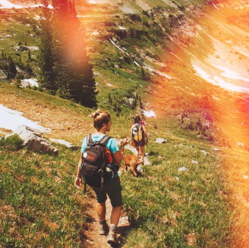 girls hiking through green mountains with light masks filter