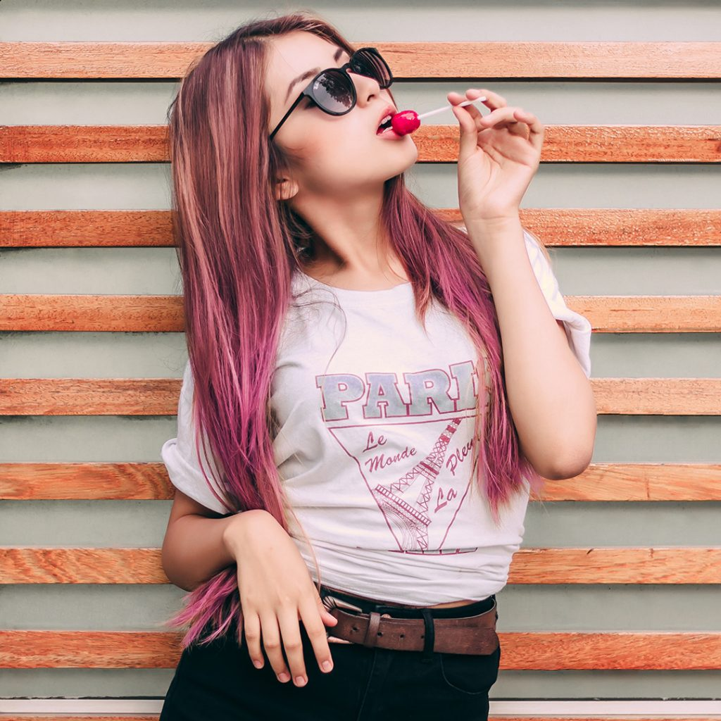 girl eating lollipop wearing sunglasses