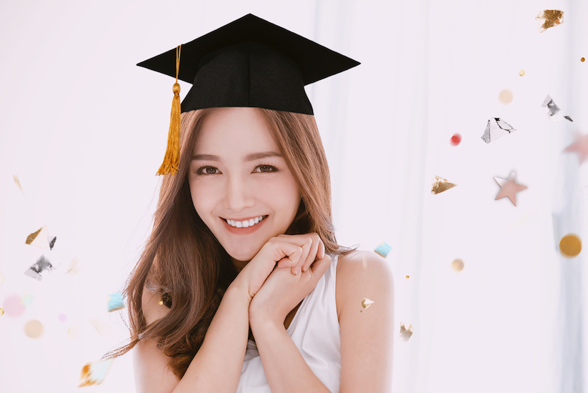 smiling asian girl with graduation sticker