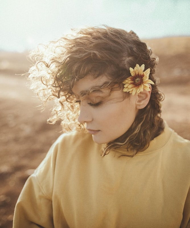 girl with yellow flower in her hair and hill in background