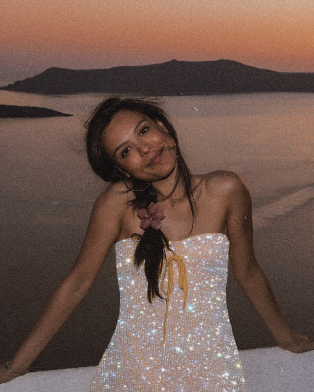 Girl in a glitter dress standing by the sea during the sunset