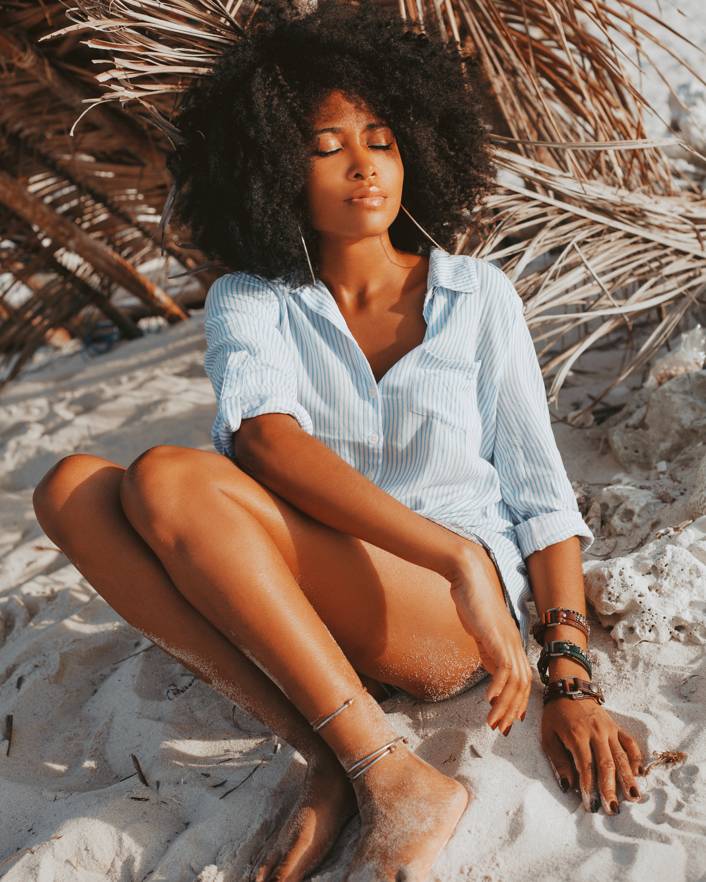 black hair girl sitting on a white sand meditating with closed eyes