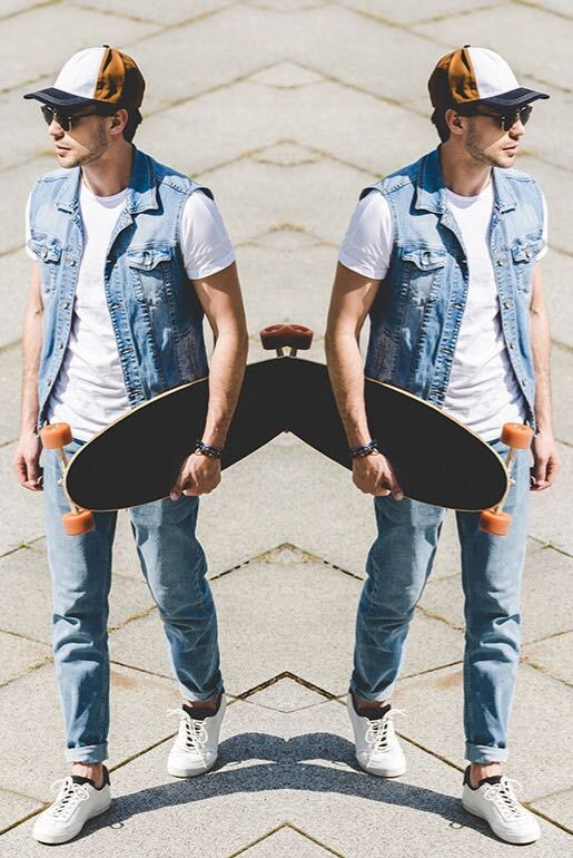 Mirror image effect on photo of man wearing jeans, vest, hat and sunglasses holding a skateboard and walking down the street made with photo editor