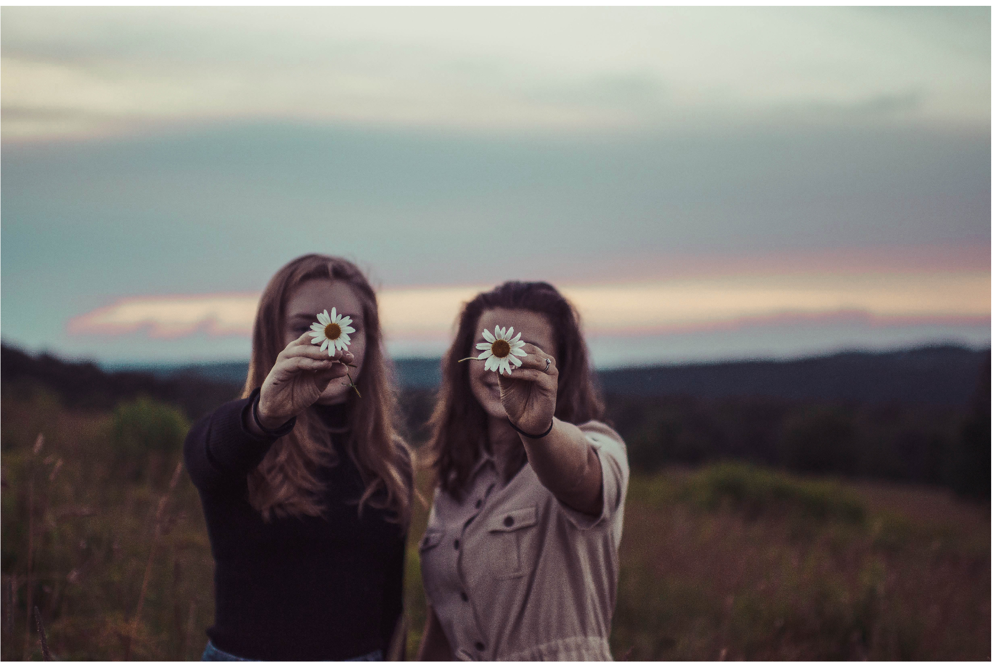 stock photo of friends holding flowers at dusk